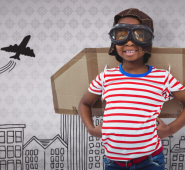 Smiling,Boy,Pretending,To,Be,Pilot,Against,Room,With,Wooden